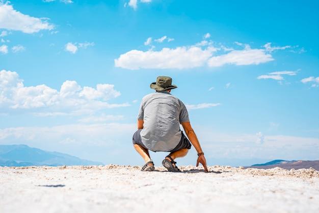 Ein junger mann hockte auf dem rücken in der weißen salzwüste im kalifornischen badwater basin. vereinigte staaten