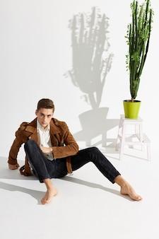 Ein junger mann im anzug sitzt barfuß auf dem boden neben einer blume in einem topf