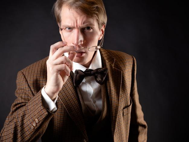 Ein junger mann im bild eines viktorianischen wissenschaftlers passt seine brille an