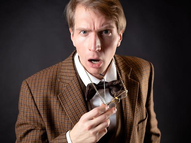 Ein junger mann im bild eines viktorianischen wissenschaftlers rückt seine brille zurecht und ist emotional überrascht. ein hochschullehrer oder ein naturwissenschaftler schaut dich geschockt an
