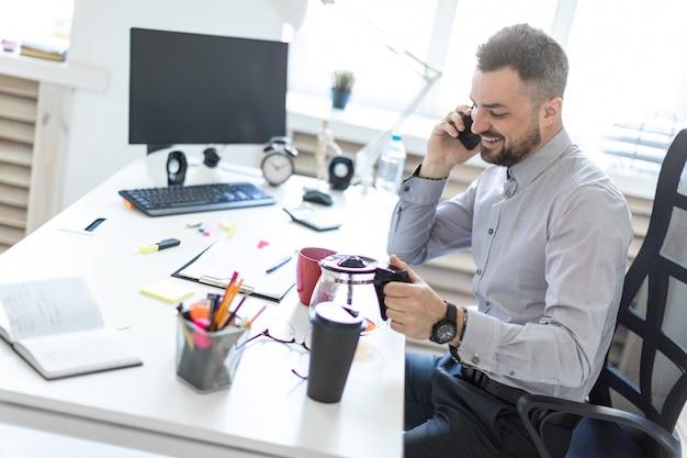 Ein junger mann im büro sitzt an einem tisch, telefoniert und gießt kaffee in eine tasse.