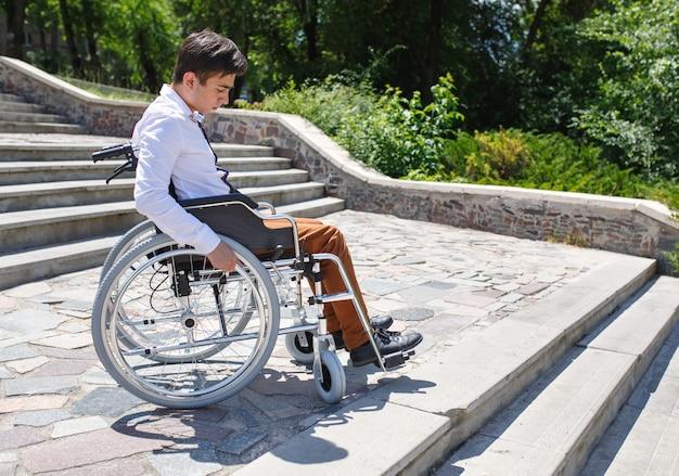 Ein junger mann im rollstuhl, der die treppe nicht hinuntersteigen kann.