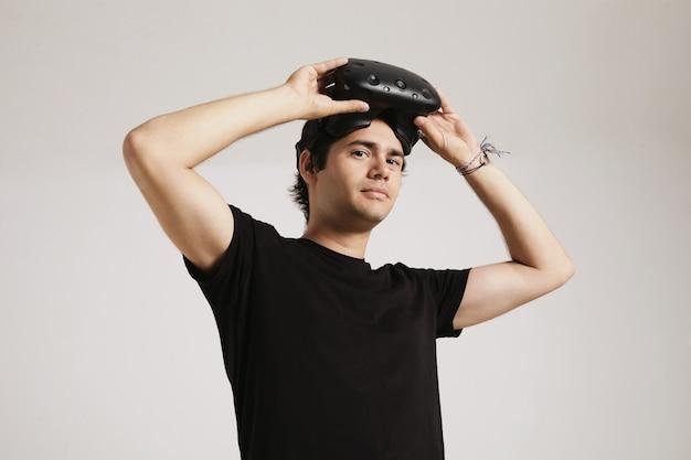 Ein junger mann im unbeschrifteten schwarzen t-shirt, das auf vr lokalisiertes vr-headset lokalisiert auf weiß