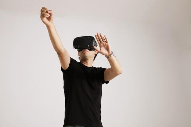 Ein junger mann im vr-headset trägt ein schlichtes schwarzes baumwoll-t-shirt, das mit seiner auf weiß isolierten umgebung interagiert