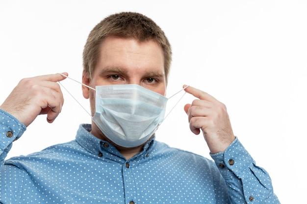 Ein junger mann in einem blauen hemd setzt eine medizinische maske auf. quarantäne während der coronavirus-pandemie.