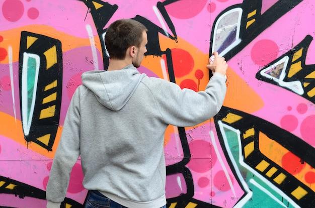 Ein junger mann in einem grauen hoodie malt graffiti in rosa und grün