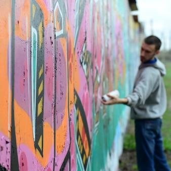 Ein junger mann in einem grauen hoodie malt graffiti in rosa und grünem c