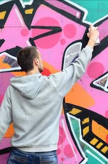 Ein junger mann in einem grauen hoodie malt graffiti