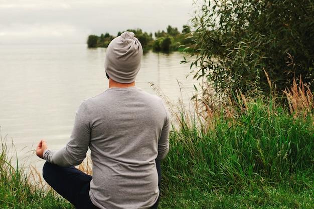 Ein junger mann in einem leichten polo sitzt am ufer. der blick von hinten. yogatraining. beschwichtigung.
