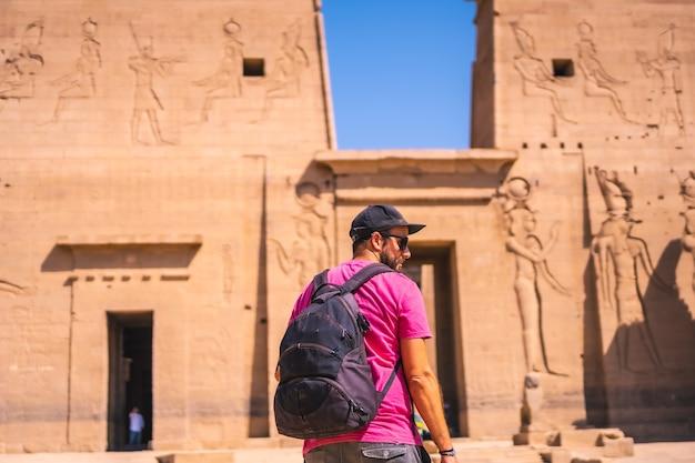 Ein junger mann in einem rosa hemd im tempel von philae, eine griechisch-römische konstruktion, ein tempel, der isis, der göttin der liebe, gewidmet ist. assuan. ägyptisch