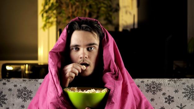 Ein junger mann in einem roten t-shirt sitzt auf der couch unter einer rosa decke, isst popcorn und sieht aufmerksam fern.