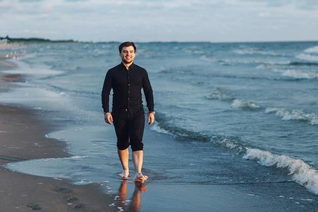 Ein junger mann in einem schwarzen hemd geht am abend an der küste entlang