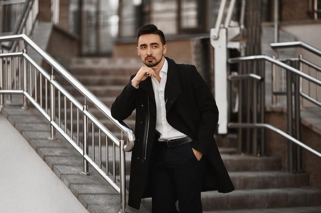 Ein junger mann in einem schwarzen mantel und einem weißen hemd, die draußen aufwerfen. hübscher geschäftsmann, der beiseite schaut und nahe der bürotreppe aufwirft.