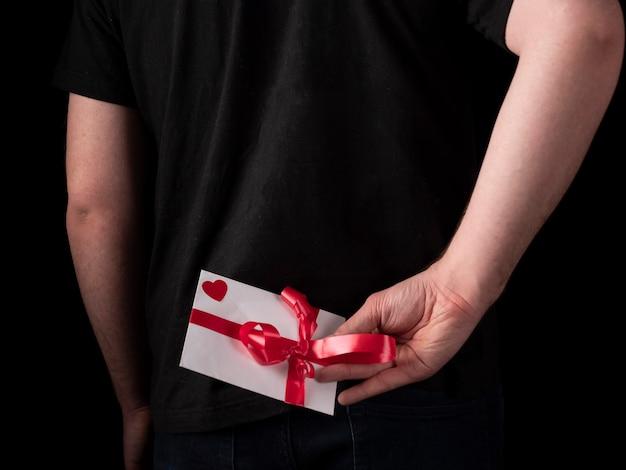 Ein junger mann in einem schwarzen t-shirt-anzug hält eine weiße karte hinter seinem rücken auf einem schwarzen
