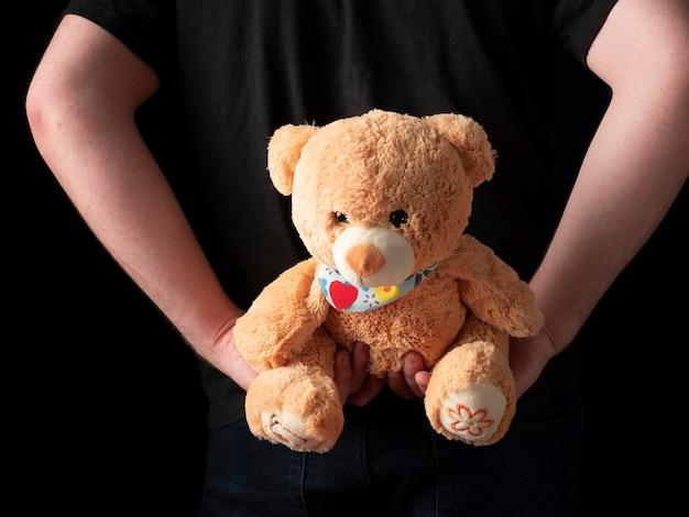 Ein junger mann in einem schwarzen t-shirt-anzug hält einen teddybären hinter seinem rücken auf einem schwarzen