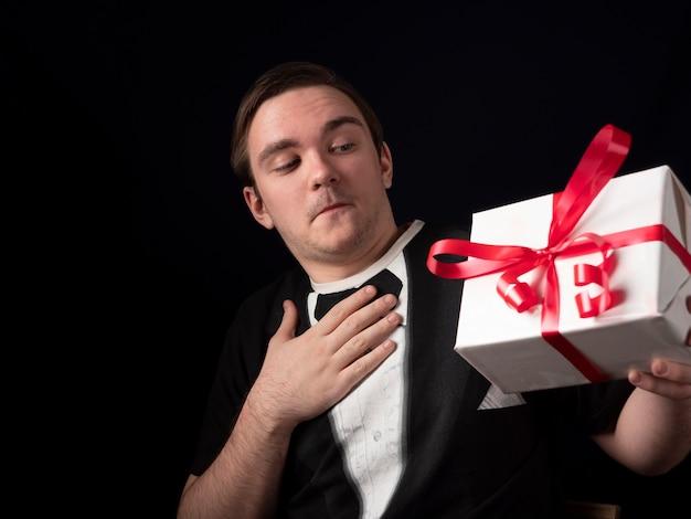 Ein junger mann in einem schwarzen t-shirt-anzug hält mit überraschung ein geschenk auf einem schwarzen