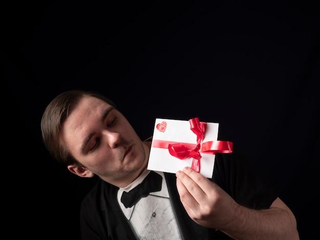 Ein junger mann in einem schwarzen t-shirt-anzug zeigt überrascht eine weiße postkarte auf einem schwarzen