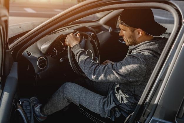 Ein junger mann in einem trainingsanzug sitzt in seinem auto.