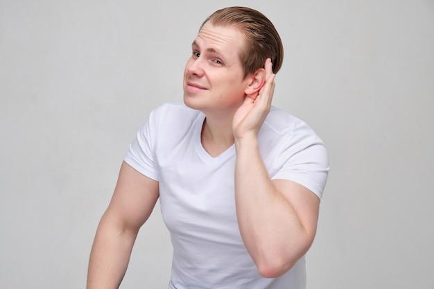 Ein junger mann in einem weißen t-shirt kann nicht gut hören. die hand ist in der nähe des ohrs.