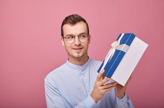 Ein junger mann in einem zart blauen hemd mit überraschung