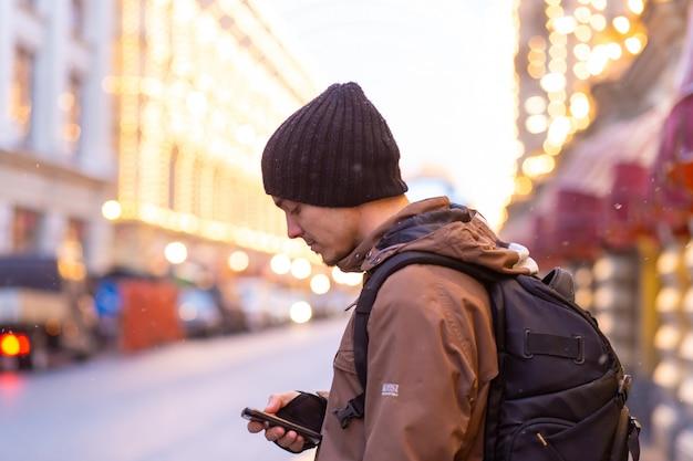 Ein junger mann in einer braunen winterjacke mit einem rucksack betrachtet das telefon