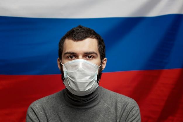 Ein junger mann in einer medizinischen maske auf dem hintergrund der russischen flagge. angst um die zukunft. nahansicht.