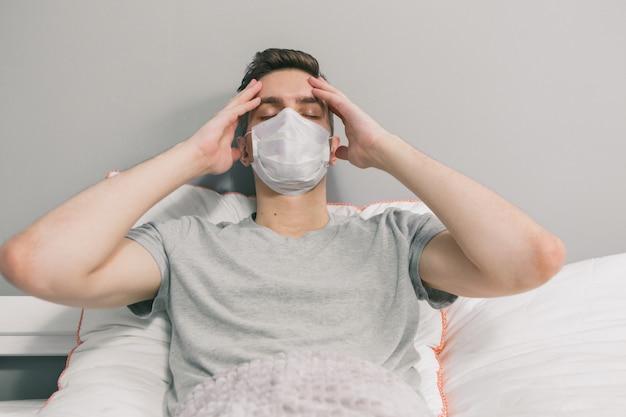Ein junger mann in einer medizinischen maske sitzt während einer epidemie in quarantäne am telefon