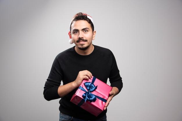 Ein junger mann in einer weihnachtsmannmütze, die ein neujahrsgeschenk hält.