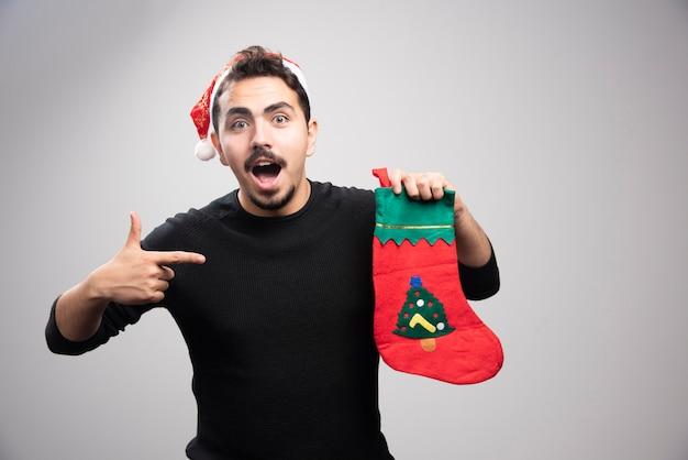 Ein junger mann in einer weihnachtsmütze, der auf eine weihnachtssocke zeigt.