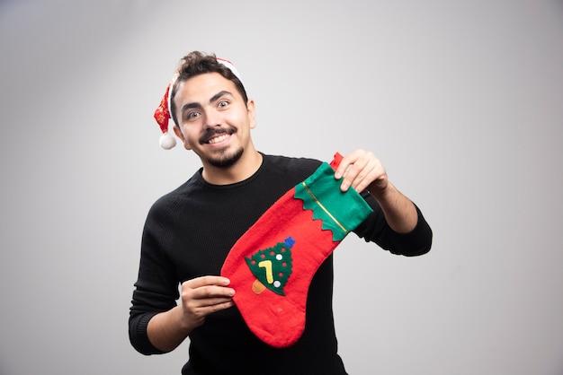 Ein junger mann in einer weihnachtsmütze, die eine weihnachtssocke hält.