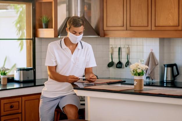 Ein junger mann in einer weißen medizinischen schutzmaske nimmt ein thermometer aus der hülle, um die temperatur seines körpers zu messen.