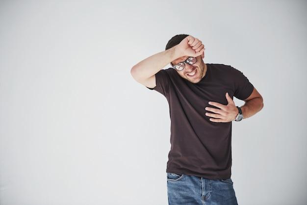 Ein junger mann in freizeitkleidung hält sich an herz und kopf fest