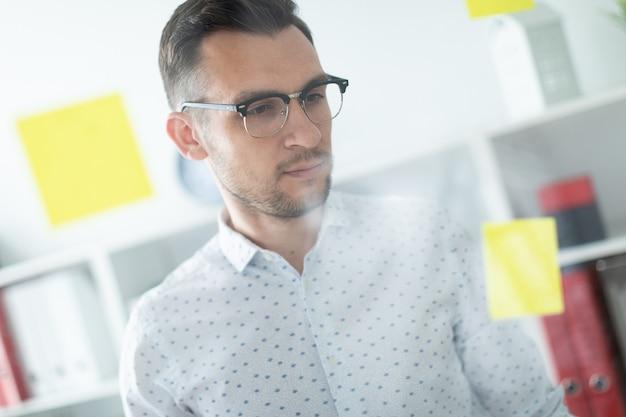 Ein junger mann in gläsern steht in der nähe eines brettes mit aufklebern.