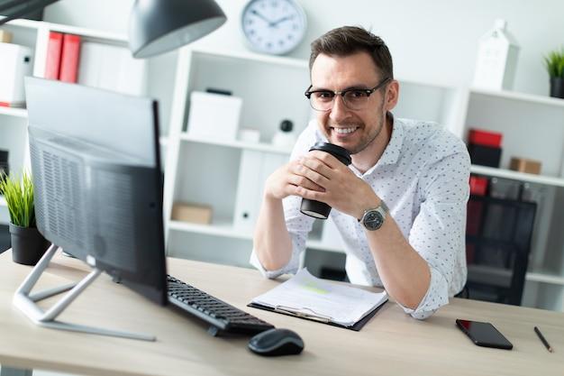 Ein junger mann in gläsern steht in der nähe eines tisches im büro und hält ein glas kaffee.