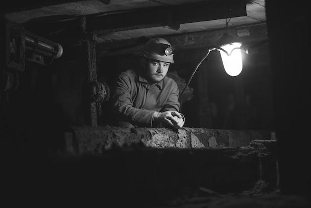 Ein junger mann in schutzanzug und helm sitzt in einem tunnel mit einem brennenden sammelalbum