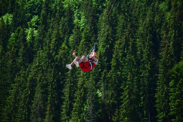 Ein junger mann ist vom bungee-jumping gesprungen und hängt nun an einem seil und filmt sich auf einer sportvideokamera vor einem verschwommenen hintergrund eines grünen waldes