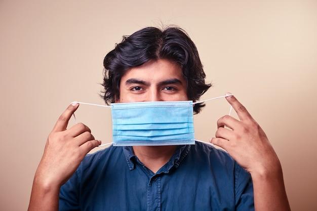 Ein junger mann lächelt, während er nitrilhandschuhe mit einer op-maske im gesicht trägt