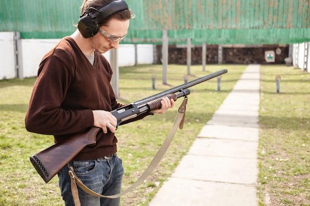 Ein junger mann lädt eine pumpaction shotgun mit einer munition auf.