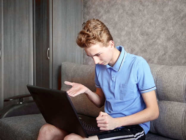 Ein junger mann lag auf dem sofa und benutzte zu hause einen laptop, fernunterricht