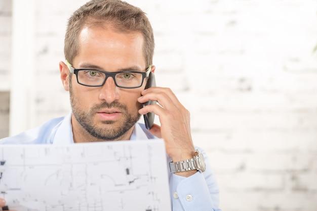 Ein junger mann liest einen plan und ein telefon