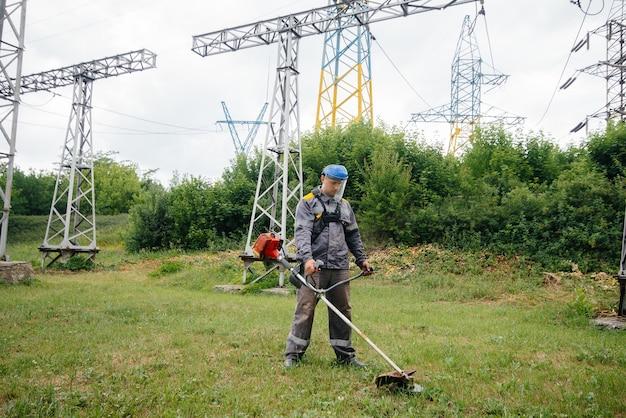 Ein junger mann mäht gras auf dem territorium eines umspannwerks in overalls. grasreinigung im betrieb, durchführung von brandschutzmaßnahmen.