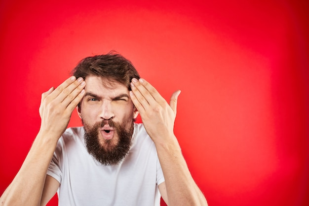 Ein junger mann mit bart im t-shirt zeigt verschiedene gefühle, spaß, traurigkeit, wut an der wand