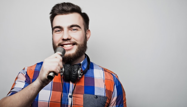 Ein junger mann mit bart trägt ein hemd mit mikrofon und singt, hipsterstyle. über grauem hintergrund.