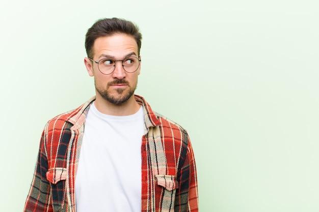 Ein junger mann mit brille posiert, während er sich wundert