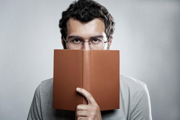 Ein junger mann mit brille und bart bedeckte sein gesicht mit einem buch. schul-und berufsbildung. nahansicht.