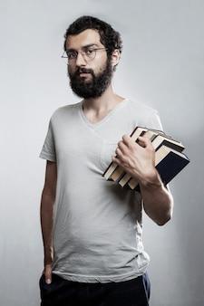Ein junger mann mit brille und bart hält einen stapel bücher in den händen. schul-und berufsbildung.