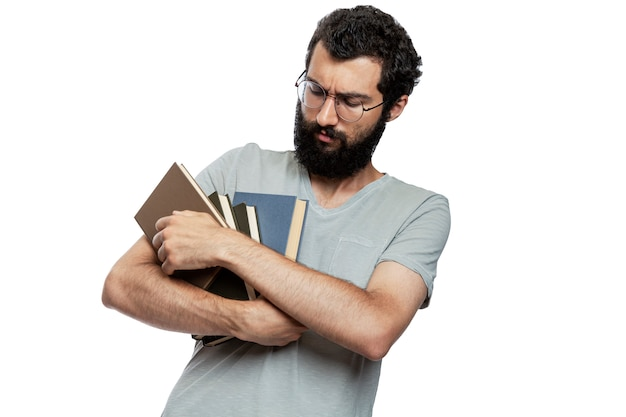 Ein junger mann mit brille und bart mit büchern in den händen und emotionen im gesicht. schul-und berufsbildung. isoliert.