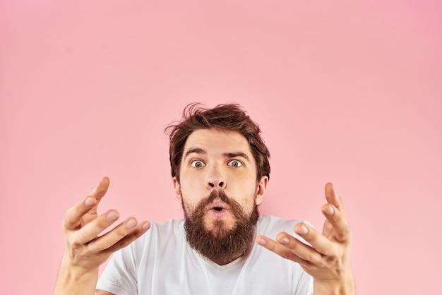 Ein junger mann mit einem bart in einem t-shirt zeigt verschiedene emotionen, spaß, traurigkeit, wut im studio im hintergrund