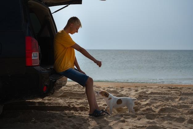 Ein junger mann mit einem geländewagen fährt und steht am ufer eines sandstrandes am meer
