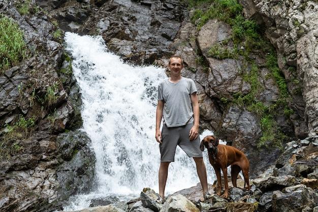 Ein junger mann mit einem hund, der in der nähe eines wasserfalls steht